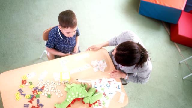 El-logopeda-de-mujer-y-el-niño-paciente-están-aprendiendo-la-pronunciación-correcta-de-las-letras-del-alfabeto