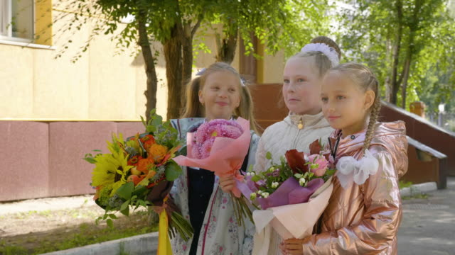 Cheerful-schoolgirls-with-flowers-talking-and-standing-near-school-together
