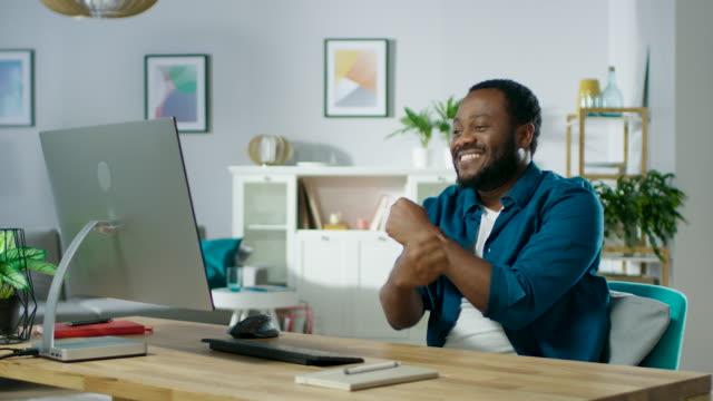 Porträt-der-schönen-African-American-Mann-tanzen-sitzend-an-seinem-Arbeitsplatz-Junger-Mann-mit-Spaß-zu-Hause-In-Zeitlupe-