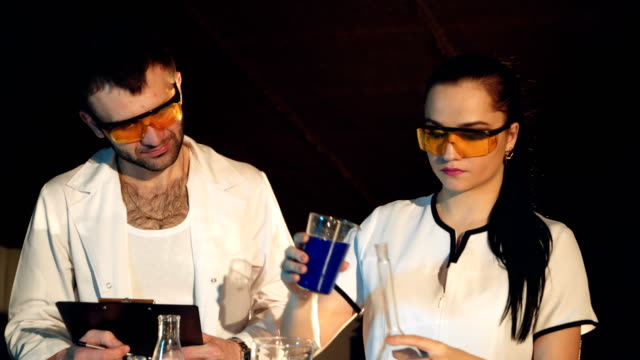 Young-female-and-male-researcher-are-doing-investigations-with-test-tubes-
