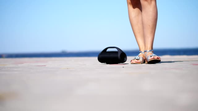 close-up-mini-music-bluetooth-portable-black-cylinder-wireless-loudspeaker-female-legs-in-silver-sandals-with-bright-red-pedicure-dancing-to-the-music-on-the-beach-in-summer