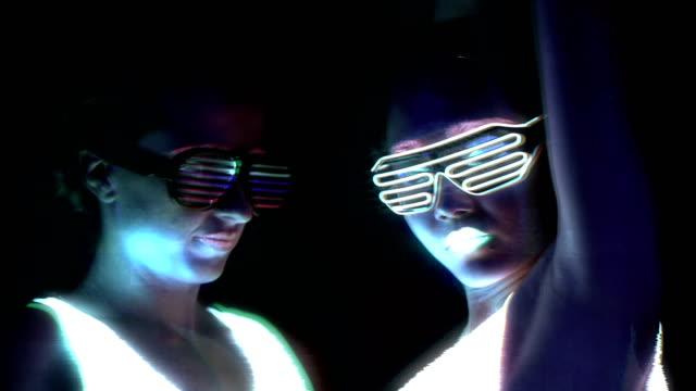 Mujeres-con-ropa-brillante-pulsera-brillante-pintura-Ultravioleta-de-la-cara-gafas-bailando-delante-de-cámara-se-enfrentan-a-tiro-Caucásica-y-la-mujer-Efectos-de-interferencia-Mujeres-