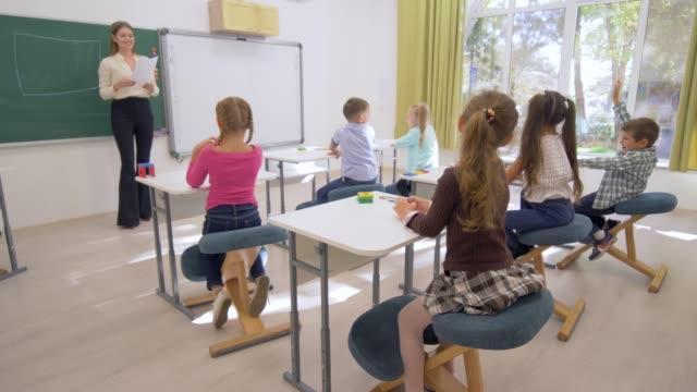 Kinder-lernen-führt-junge-Lehrerin-Dame-in-der-Nähe-von-Board-kognitive-Lektion-für-nette-Schüler-am-Schreibtisch-im-Klassenzimmer-der-Schule