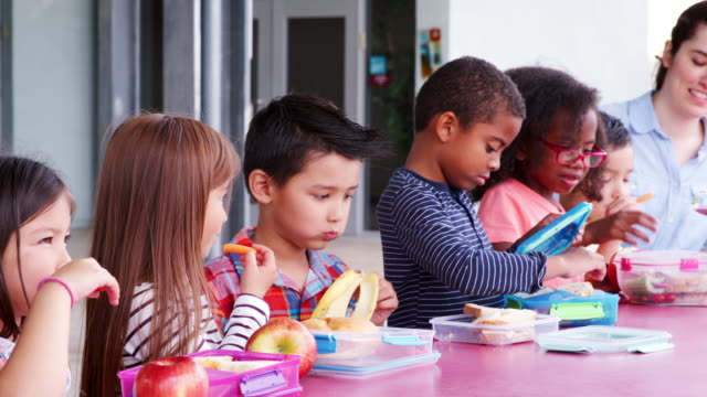 Escuela-primaria-niños-comiendo-en-la-mesa-con-comidas