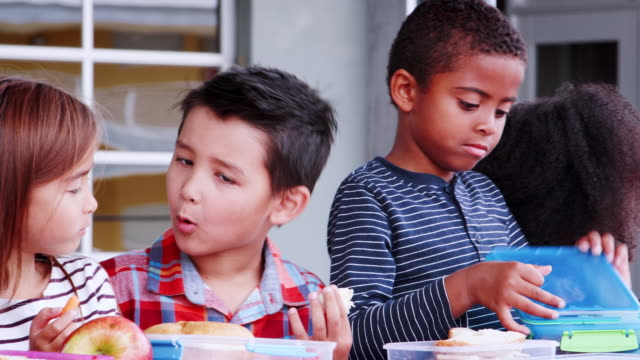 Los-niños-de-primaria-y-maestro-en-una-mesa-en-el-almuerzo