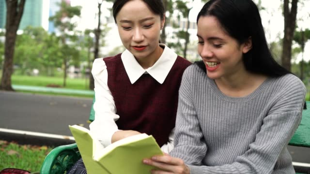 Two-young-female-friends-talking-and-discussing-with-each-other-in-public-park-outdoors-Asian-and-Caucasian-diversity-