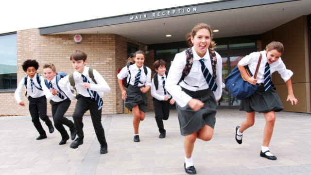 Group-Of-High-School-Students-Wearing-Uniform-Running-Out-Of-School-Buildings-Towards-Camera-At-The-End-Of-Class