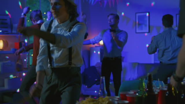 At-the-College-House-Costume-Party:-Diverse-Group-of-Friends-Have-Fun-Dancing-and-Socializing-and-Drinking-Stylish-Boys-and-Girls-Dance-in-the-Living-Room-In-Slow-Motion-