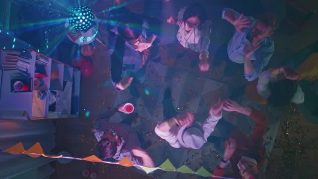 En-la-fiesta-del-Colegio:-grupo-diverso-de-amigos-divertirse-bailar-socializar-y-beber-Jóvenes-con-estilo-danza-enérgio-en-la-sala-de-estar-Disco-luces-de-neón-Arriba-hacia-abajo-de-golpe-