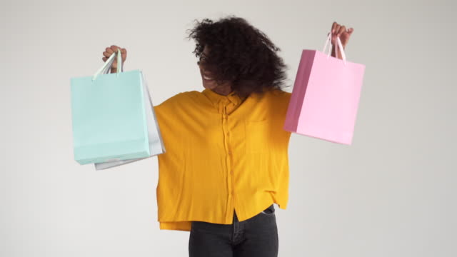African-american-woman-holding-shopping-bags-and-dancing