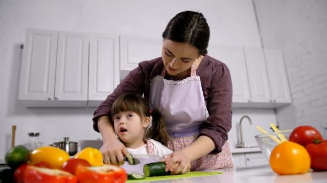 Niño-con-discapacidad-síndrome-de-down-con-madre-cocina