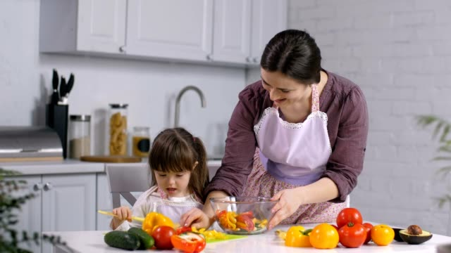 Girl-with-special-needs-helping-mom-preparing-salad