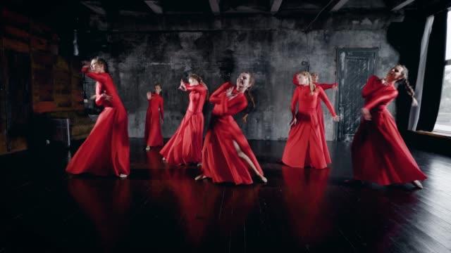 siete-mujeres-encantadoras-de-bailarines-están-bailando-en-la-sala-de-ensayo-llevando-vestidos-de-rojo-en-suelo