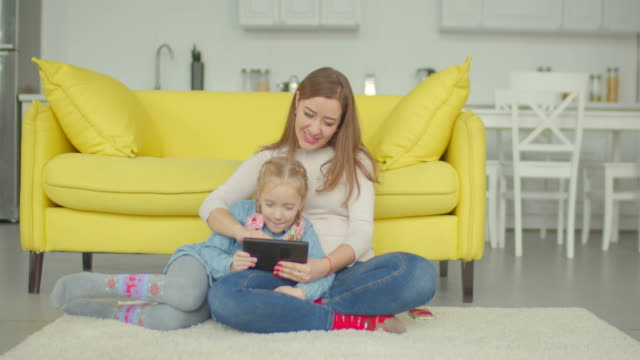 Carefree-mom-and-girl-playing-online-with-tablet-pc