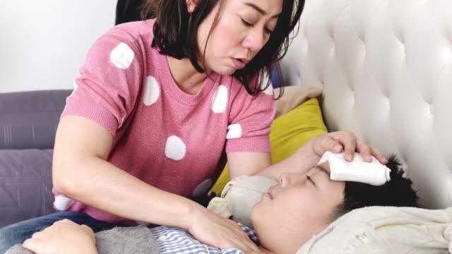 Niño-Asiático-enfermo-acostado-en-la-cama-comprobando-su-temperatura-lenta-de-madre-e-hijo-en-la-casa-de-la-madre-