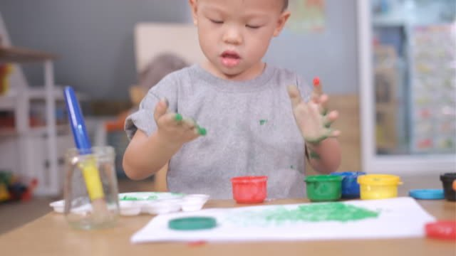 Asian-2--3-years-old-toddler-baby-boy-child-finger-painting-with-hands-and-watercolors