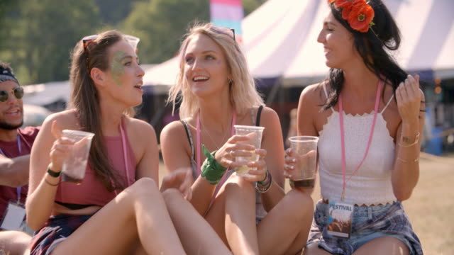Three-female-friends-sitting-on-grass-at-a-music-festival