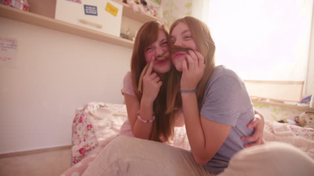 Girls-on-a-bed-holding-each-other-s-hair-as-moustaches