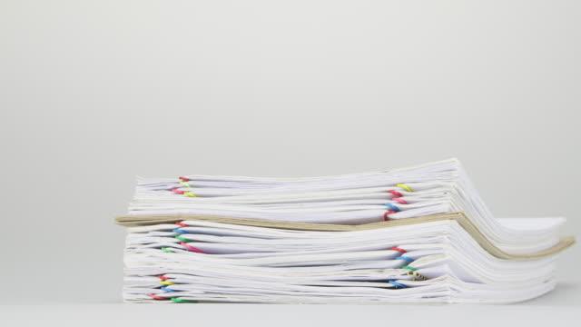 Pila-de-sobrecarga-papeleo-y-sobre-la-mesa-tiempo-lapso-en-blanco