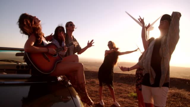 Hipster-amigos-disfrutando-de-viaje-con-una-guitarra-durante-la-puesta-del-sol