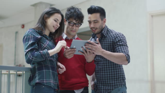 Group-of-young-multi-ethnic-students-are-using-a-tablet-computer-in-an-university-