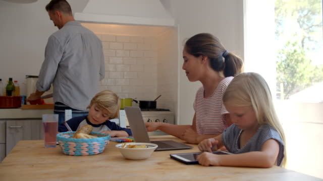 Kids-at-kitchen-table-with-mum-while-dad-cooks