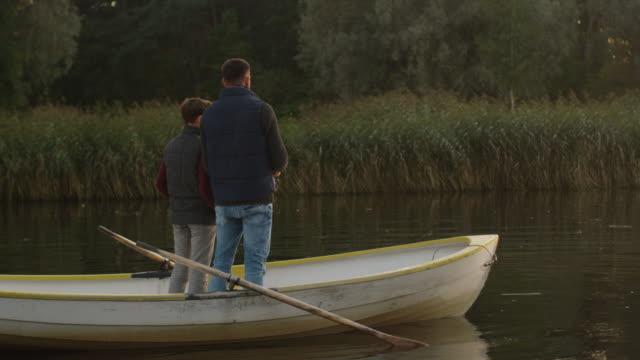 Padre-e-hijo-están-de-pie-en-el-barco-y-pesca-