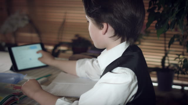 4K-Hi-Tech-Shot-of-a-Child-Doing-Homework-with-Help-from-Tablet
