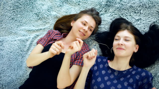 Top-view-of-two-beautiful-girls-in-headphones-listening-music-dancing-and-smiling-while-lying-on-bed