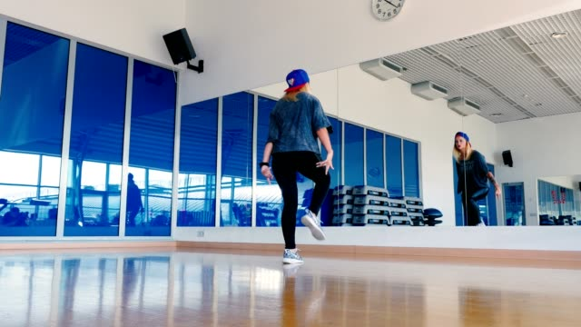 Young-girl-in-cap-dancing-hip-hop-in-front-of-the-mirror-in-gym