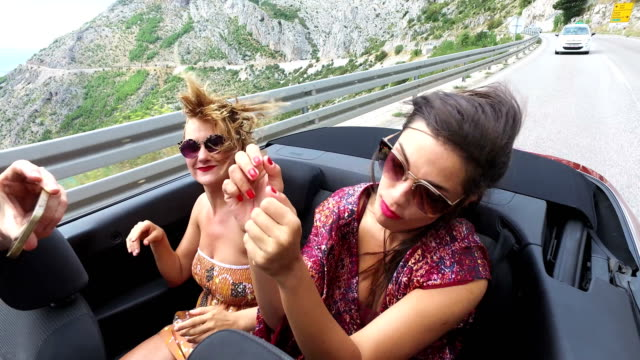 Two-happy-girls-partying-while-riding-in-cabriolet