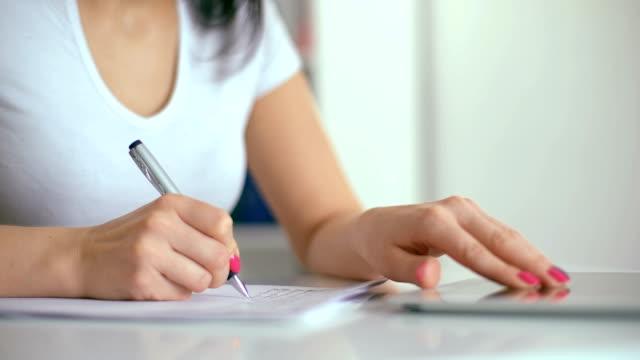 Mano-femenina-con-pluma-de-escribir-en-el-cuaderno