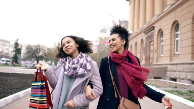 Dolly-shot-of-two-attractive-mixed-race-women-dancing-and-have-fun-while-walking-down-the-street-with-shopping-bags-Happy-young-friends-walk-after-visiting-mall-sale