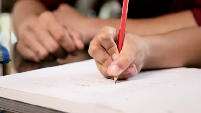 Closeup-Of-Young-Girl-Hand-Writing-Pencil-On-Exercise-Book