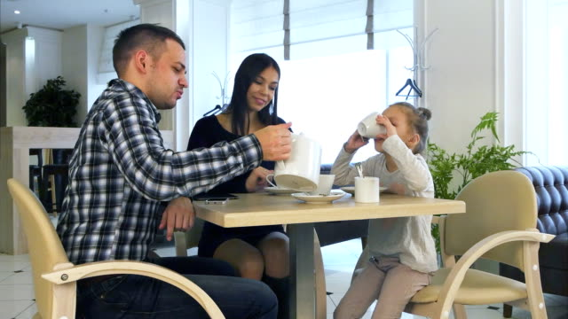 Young-family-in-casual-clothes-drinking-tea-in-cafe-talking-and-relaxing-together