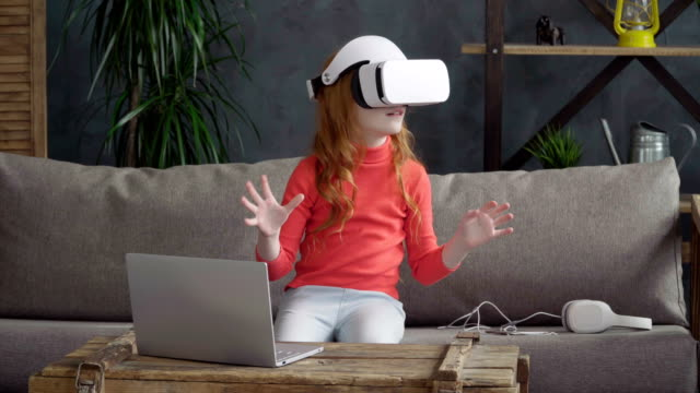 Little-girl-is-sitting-on-the-sofa-in-the-room-in-vr-headset-and-dong-something-with-the-hands