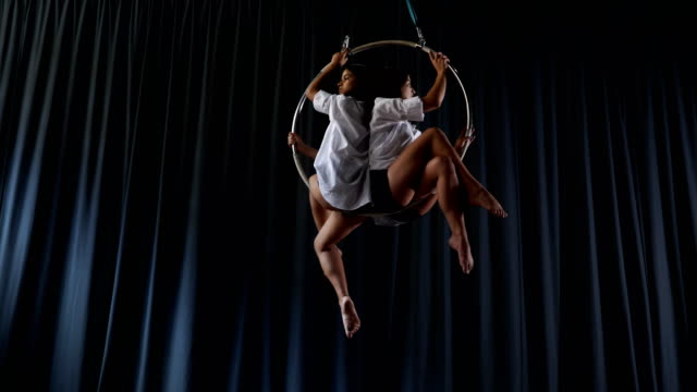 Charming-gymnasts-sits-and-spins-in-the-aerial-hoop