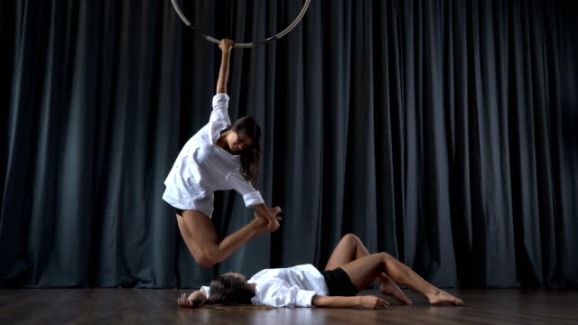 Beautiful-girl-warms-up-on-the-aerial-hoop-her-friend-lays-on-floor