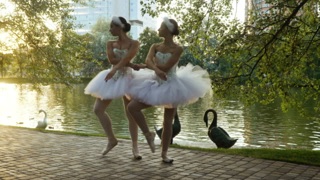 Beautiful-ballerinas-dances-in-park-near-the-pond-with-swans-on-the-background