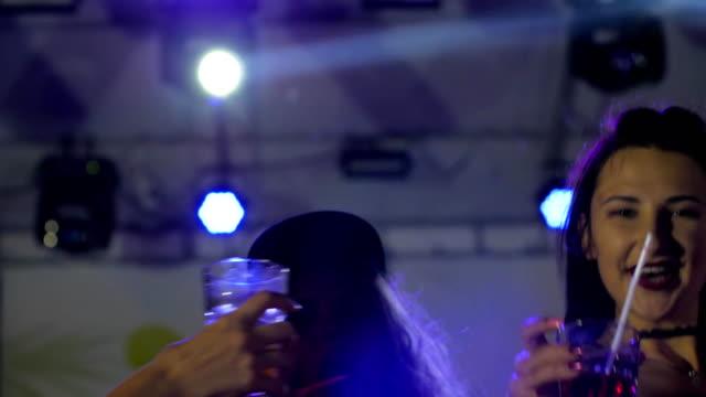 amigas-brindando-con-cócteles-divertirse-en-el-club-de-noche-las-niñas-disfrutar-de-danza-con-bebidas-hacen-tostadas-en-partido