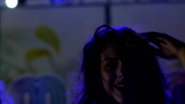 close-up-happy-girl-dance-at-night-club-with-glass-cocktail-beautiful-woman-with-beverage-on-party-in-blue-lights