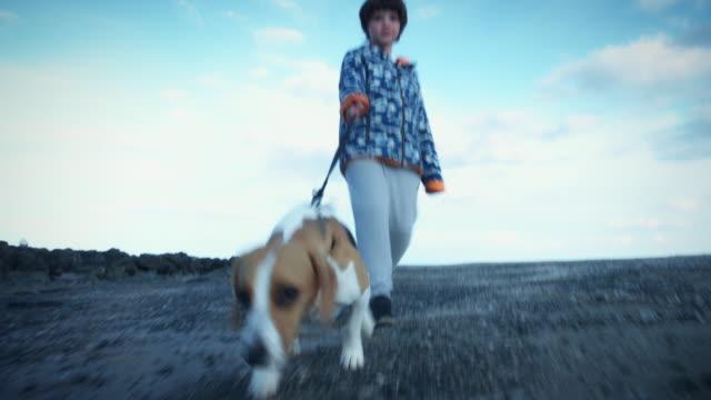 4K-al-aire-libre-playa-niño-y-perro-caminando-a-cámara