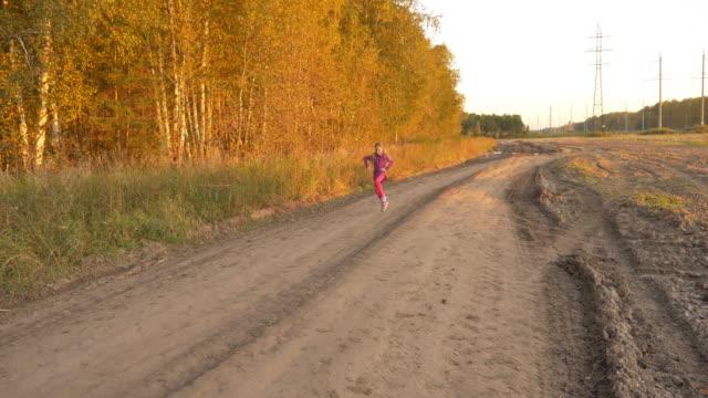 Chica-corriendo-y-girando-en-carretera-tarde-otoño-Jovencita-al-aire-libre-panorámica-de-longitud-total-