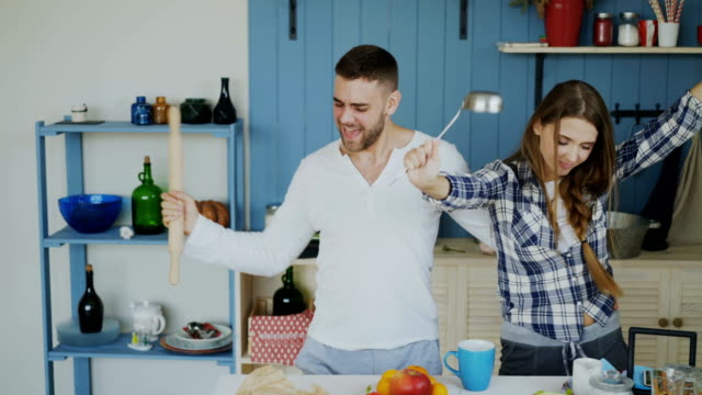 Young-joyful-couple-have-fun-dancing-and-singing-while-set-the-table-for-breakfast-in-the-kitchen-at-home