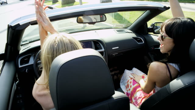 Caucasian-girls-enjoying-glamorous-lifestyle-driving-luxury-car