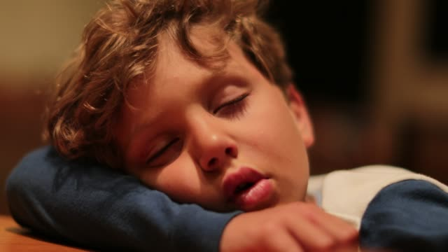 Closeup-of-drooling-sleepy-child-slouched-on-desk-exhausted-Young-boy-sleeping-profoundly