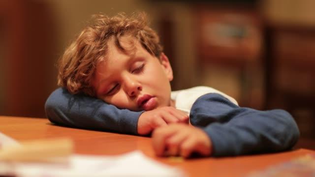 Verschlafenes-Kind-müde-schlief-mit-Kopf-auf-Tisch-Kleiner-Junge-schlafen-nach-einem-langen-Tag-erschöpft-von-den-Aktivitäten-des-Tages