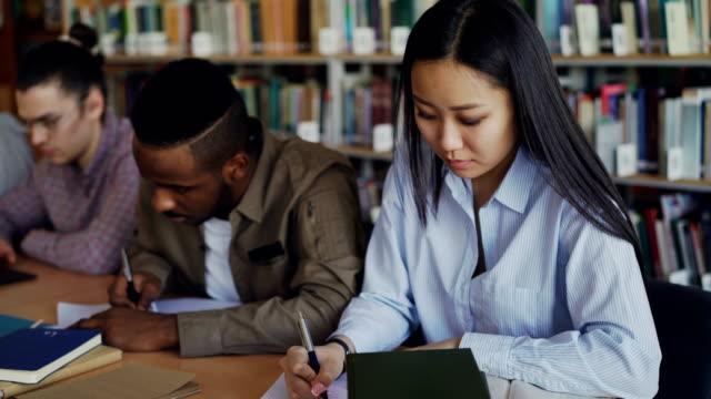 Estudiante-chica-preparándose-para-el-examen-y-escribir-notas-mientras-está-sentado-en-la-mesa-en-la-biblioteca-de-la-Universidad-con-sus-compañeros-de-clase-estudiando-libros-de-concentrado