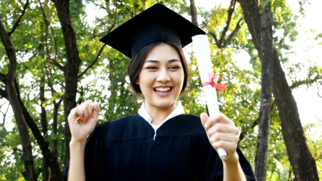 Young-Asian-Woman-Students-wearing-Graduation-hat-and-gown-Garden-background-Woman-with-Graduation-Concept-