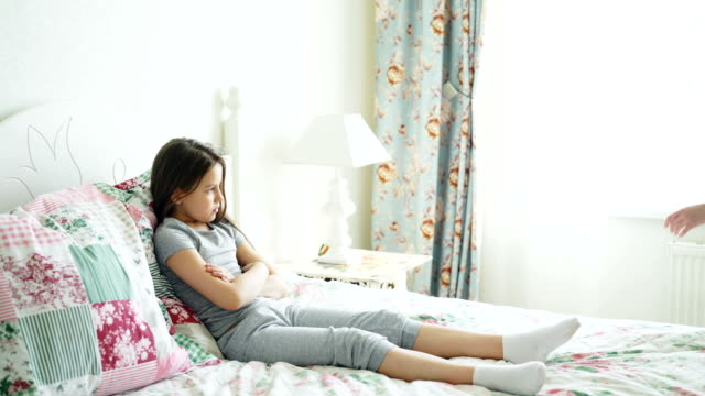Angry-mother-argue-scolding-her-upset-little-daughter-lying-on-bed-in-bright-bedroom-at-home